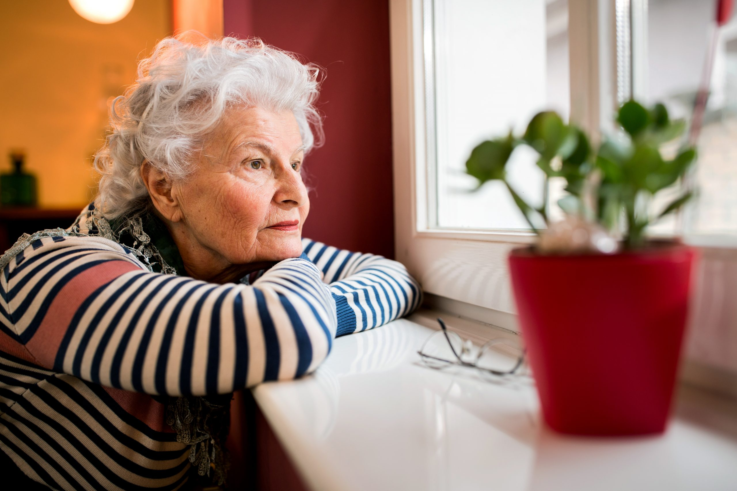 Sad alone senior woman looking through window at home
