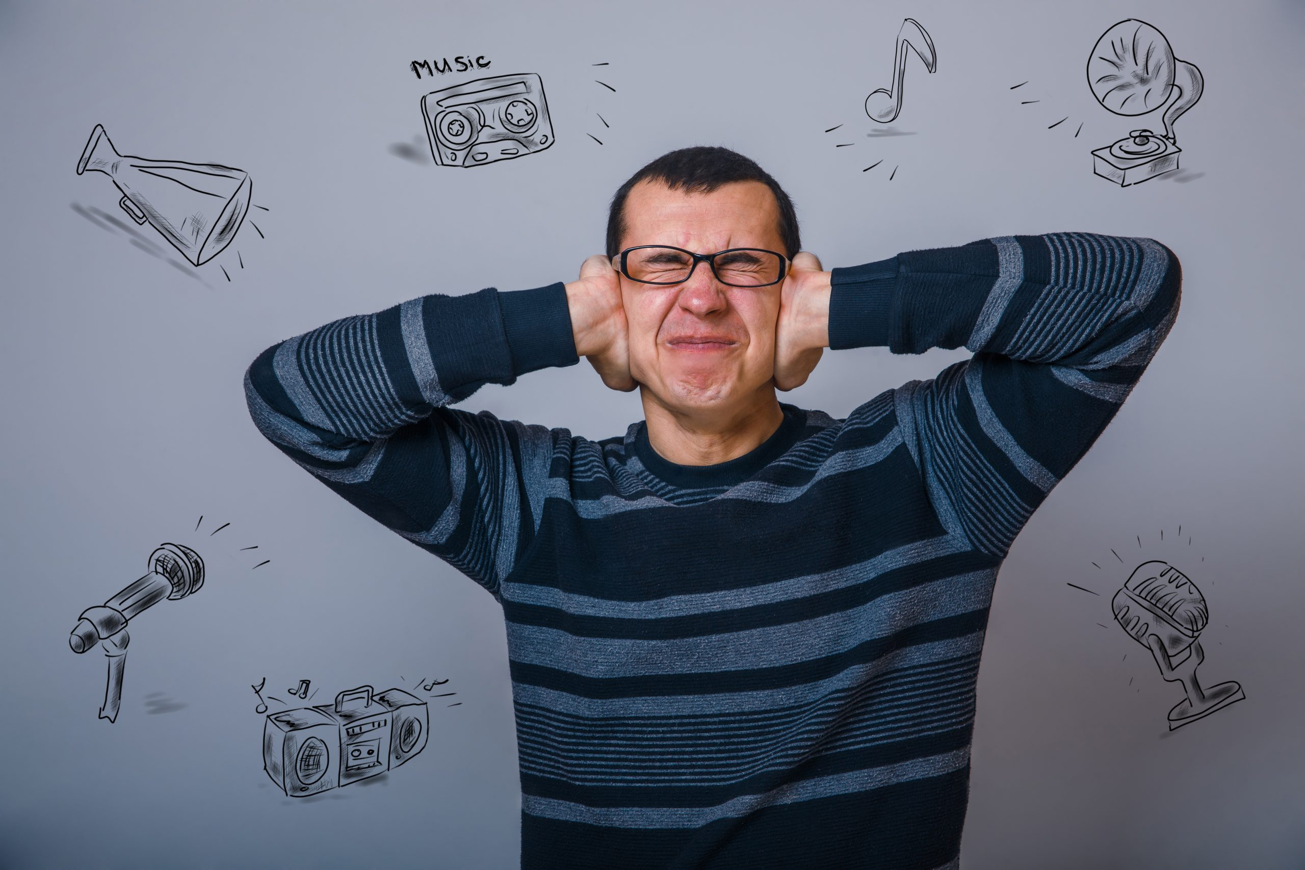 man of thirty years in glasses covering his ears, in front of grey background covered with sketches of vaarious sources of loud sounds.